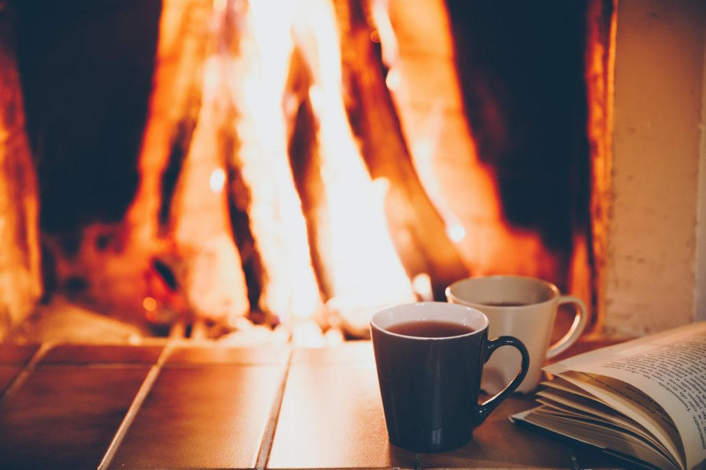 Two cups and Open book by Fireplace